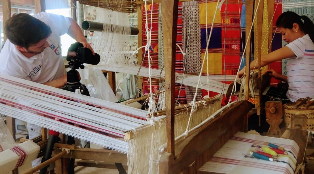 Business intern photographs a female staff member weaving material for a product at a workshop in Vietnam.